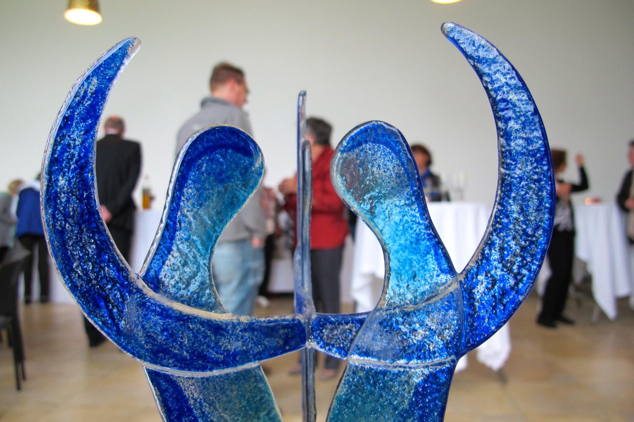 Eine Blaue Skulptur, im Hintergrund eine Veranstaltung